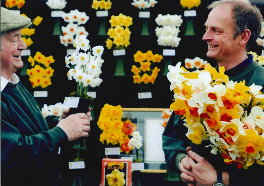man holding a bunch of daffodils