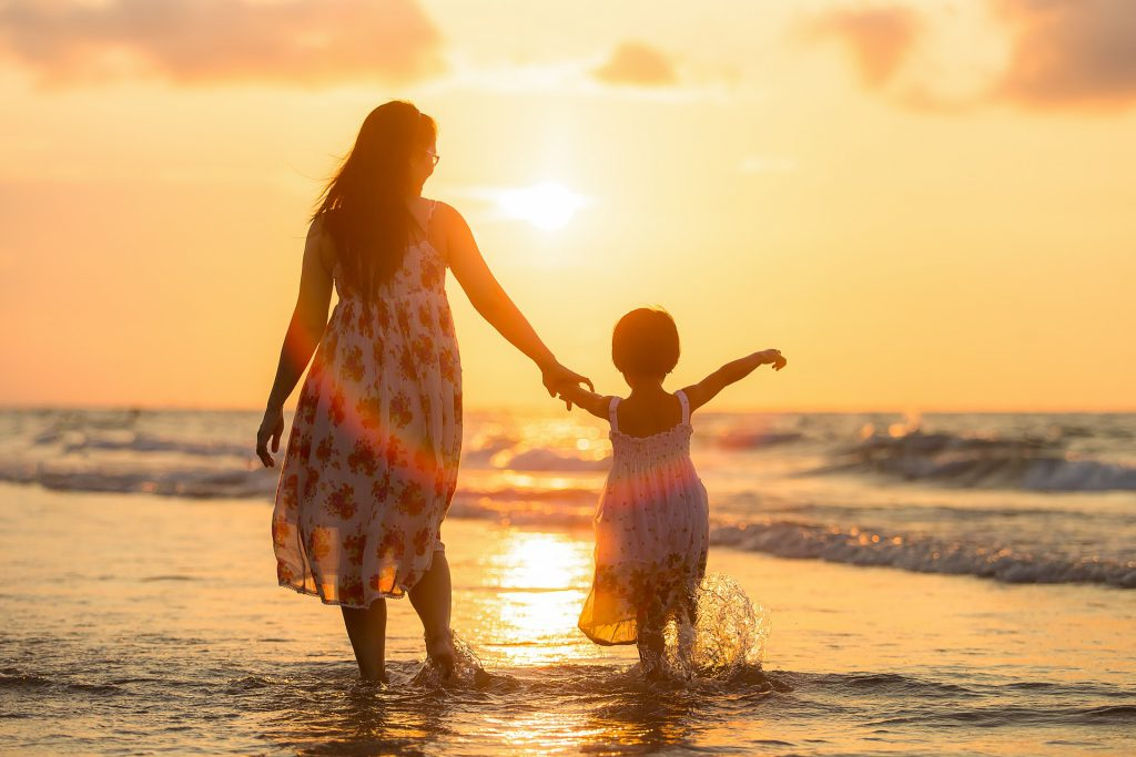 Mother and daughter playing in the sea at sunset