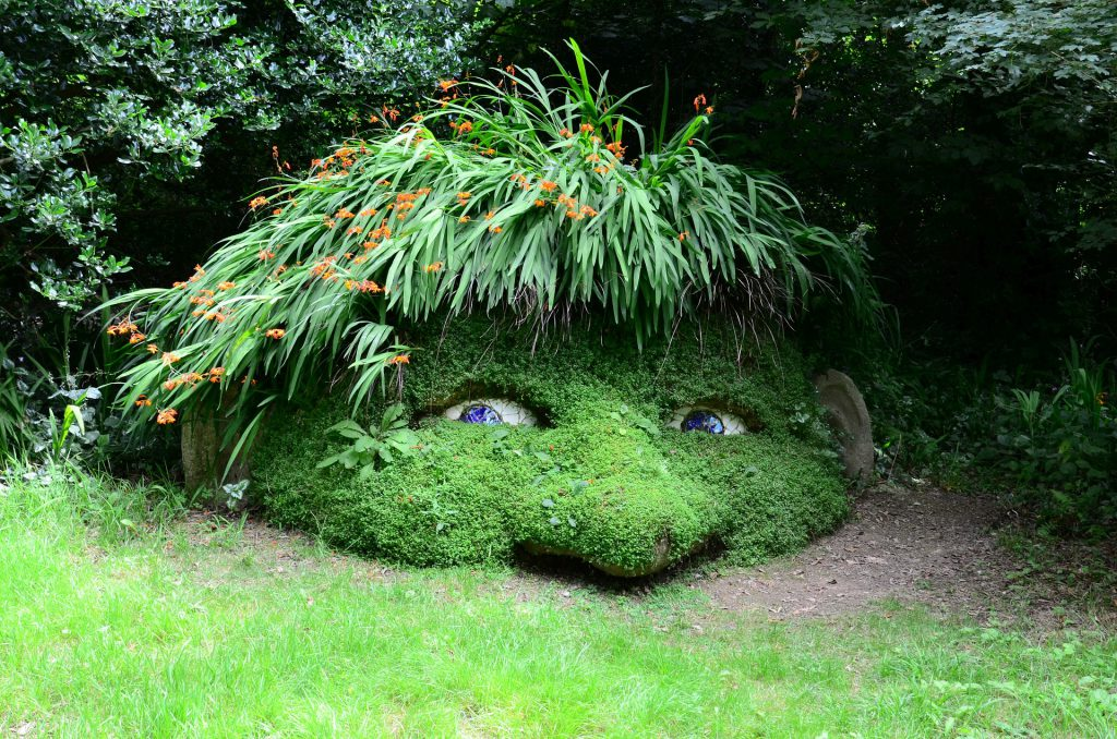 Unusual garden sculpture of a head at the Lost Gardens of Heligan, in Cornwall