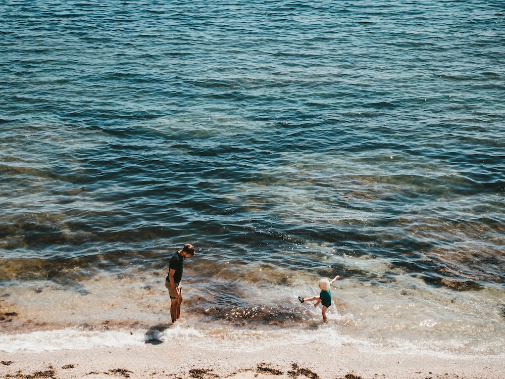 A father and son playing in the sea at a beach in Cornwall
