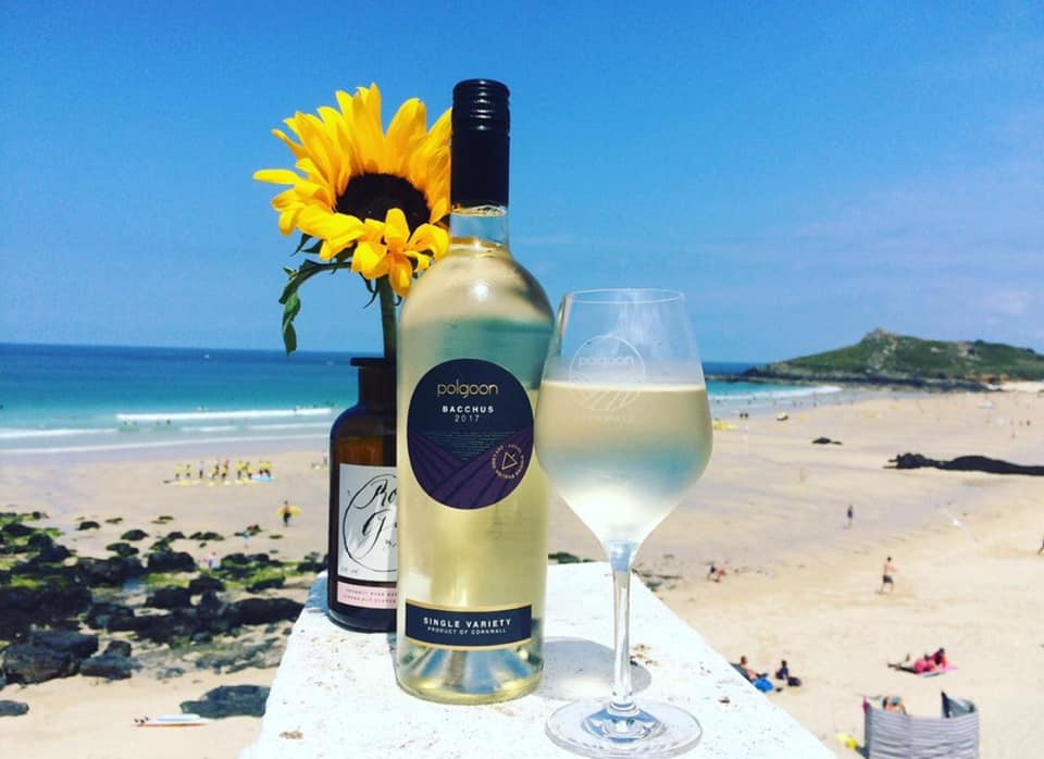 A bottle of Polgoon wine and glass on a table, with the views of a Cornish beach in the background.