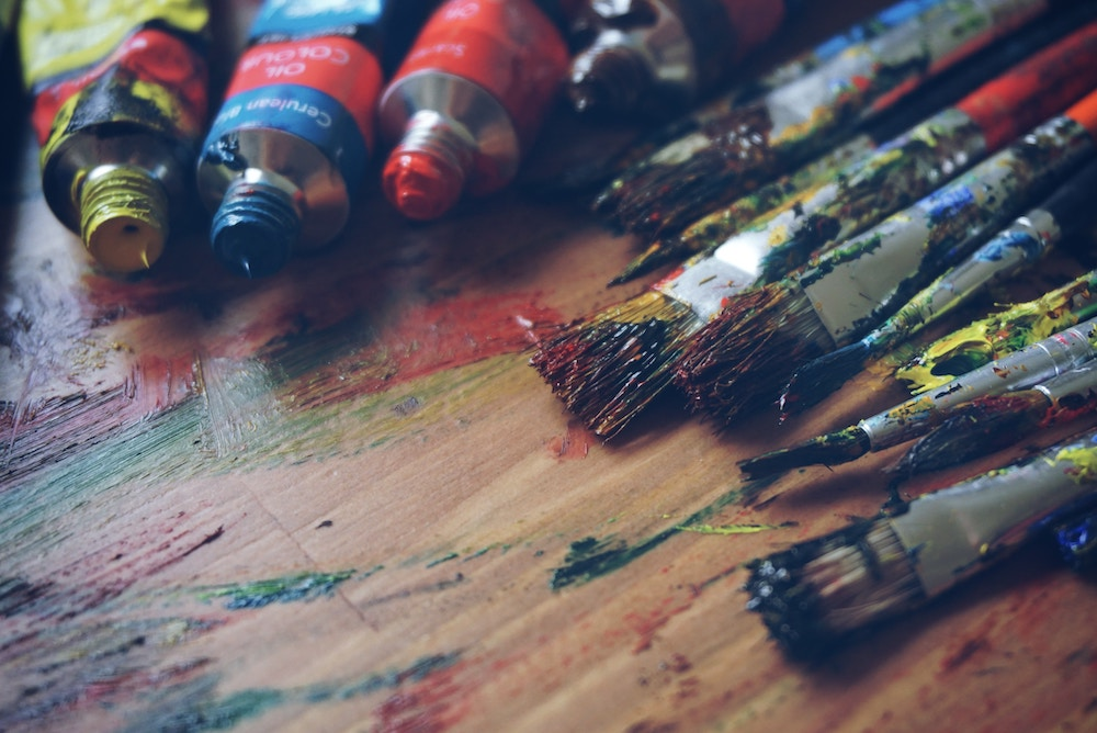 Multiple paintbrushes and different coloured paints