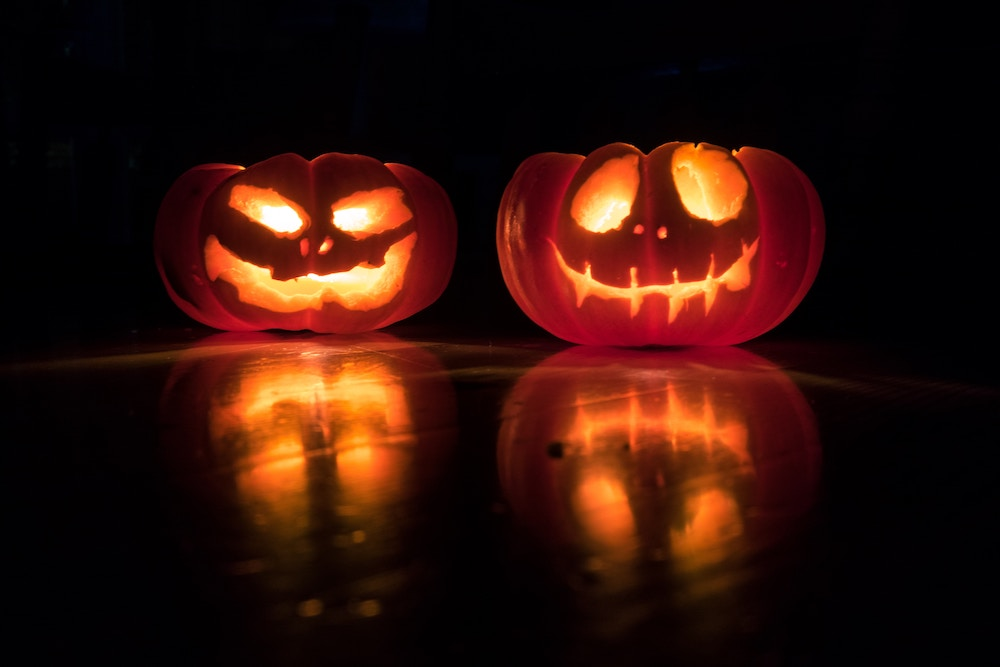 Two carved pumpkins lit up