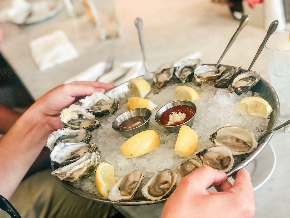 A dish of oysters, lemon and dipping sauces