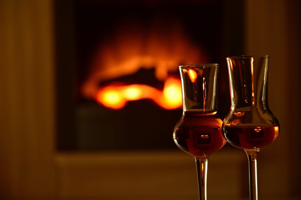 Two glasses of whiskey in front of a fire.
