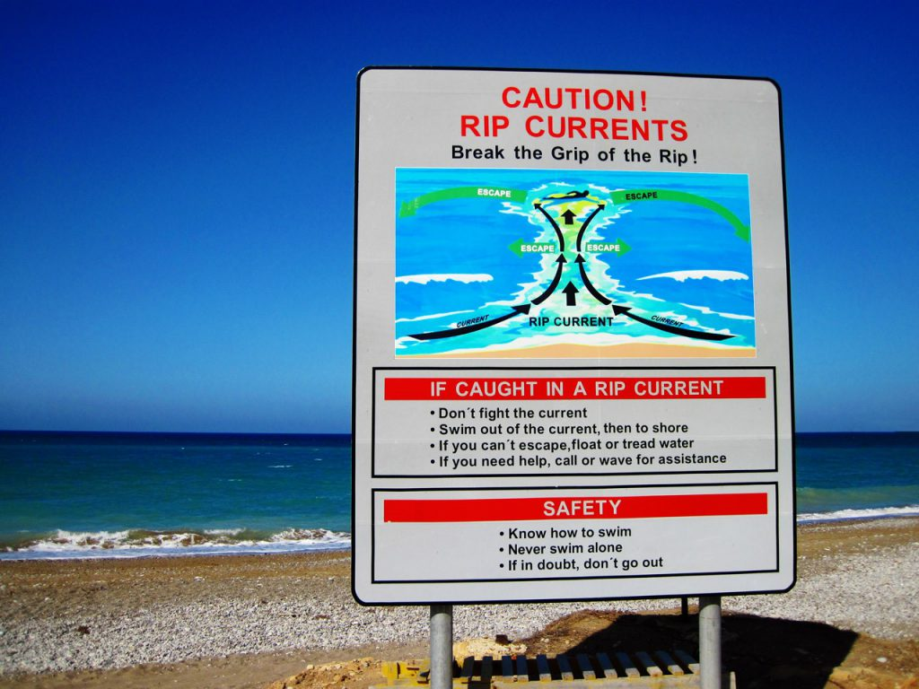 sign on a beach warning of rip currents