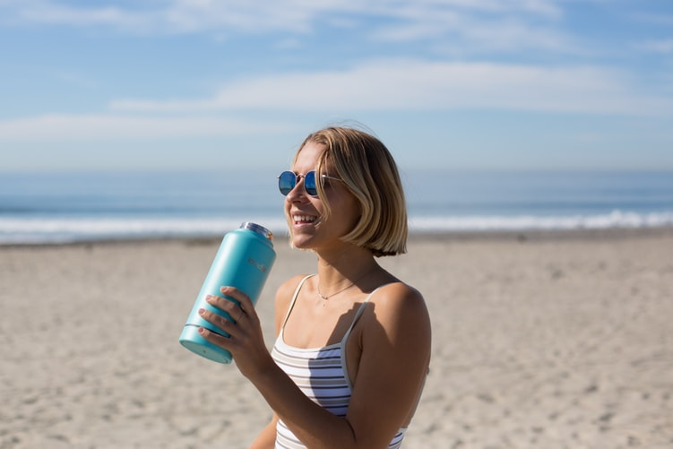 Woman holding a water bottle on the beach