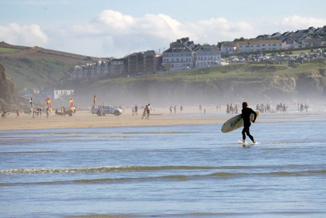 A person with a surfboard running along the coast at St. Ives in Cornwall
