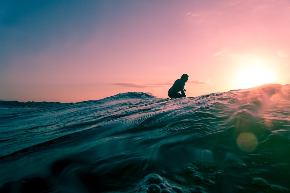 A surfer catching a wave in a purple sunset