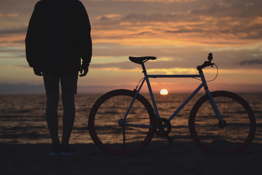 A man stood next to his bike looking at the beach