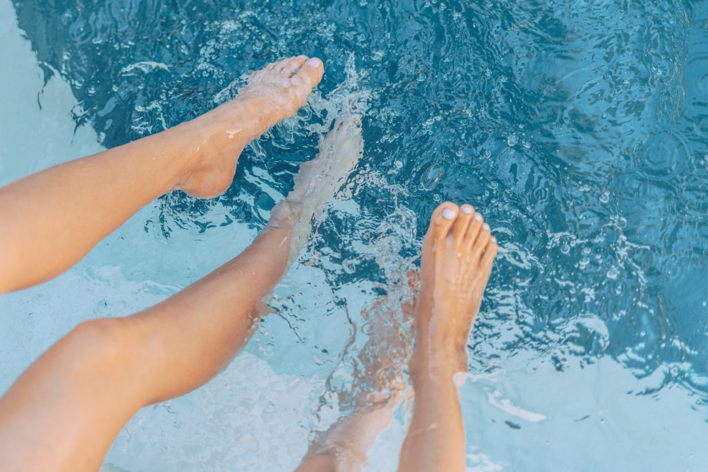 Two pairs of feet in a swimming pool