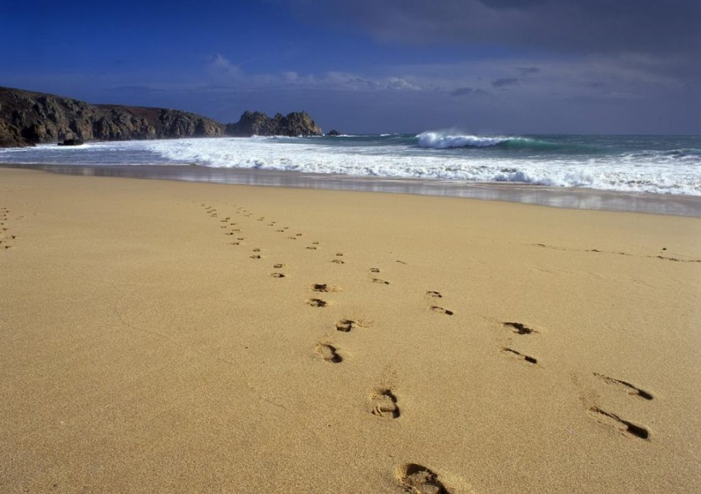 Footprints in the sand at Porthcurno beach
