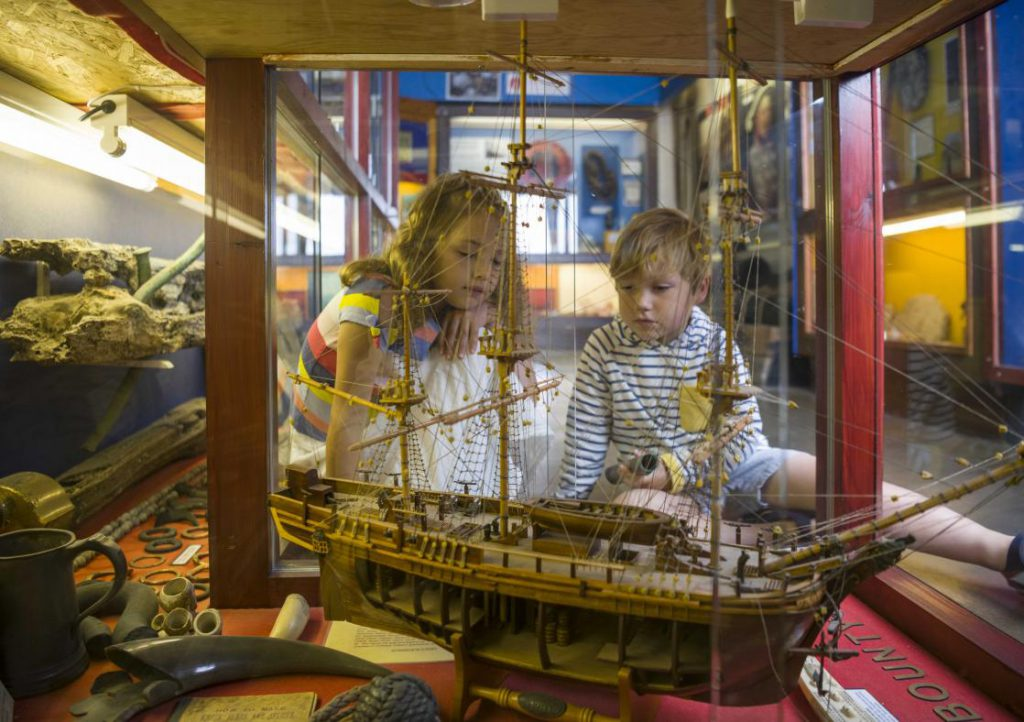 Two children looking at a model ship