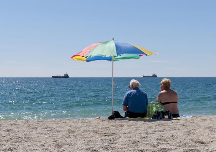 An elderly couple watching the boats at Gyllyngvase Beach