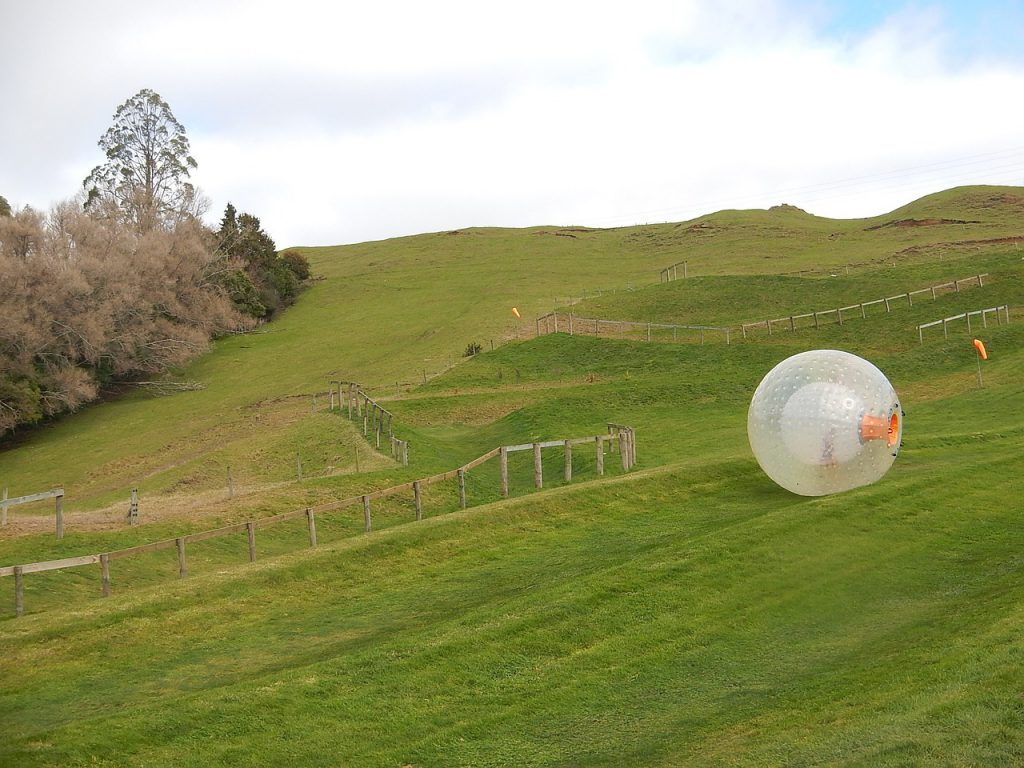 A zorbing ball rolling down a hill