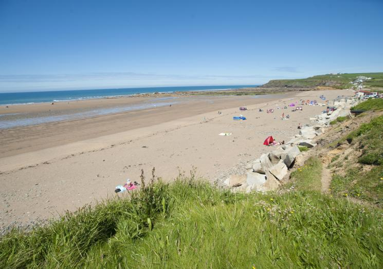 A mostly empty Widemouth Bay on a clear day