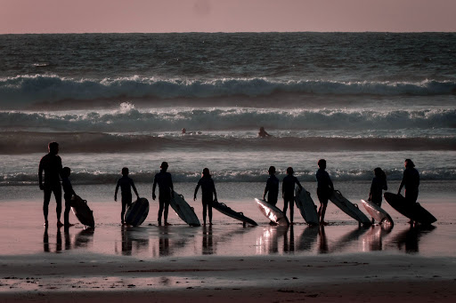 People standing with surfboards on a beach